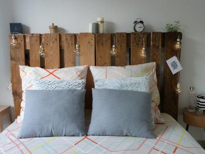 une tête de lit en palette décorée avec de petites lampes