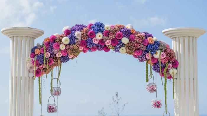 arche fleurie mariage avec des colones construite en plein air