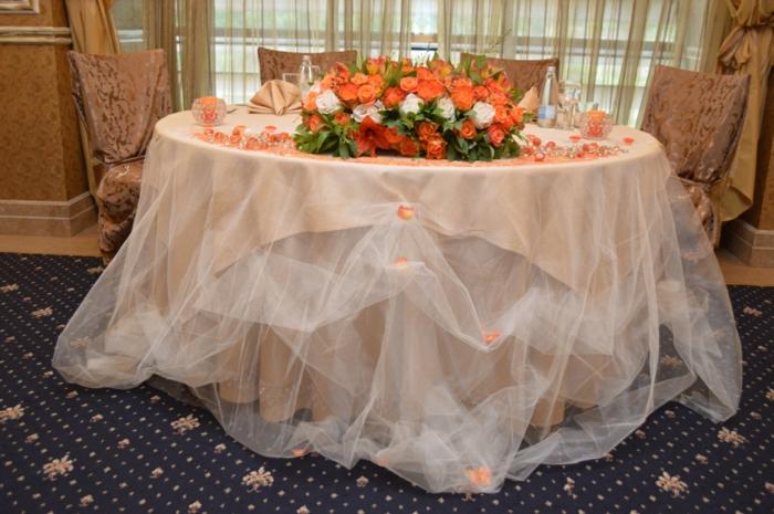 table des amoureux et des témoins avec une couverture élégante et des fleurs oranges