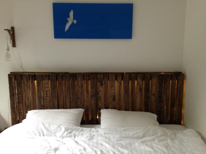 tête de lit en palette à faire soi-même avec de petites lampes comme déco