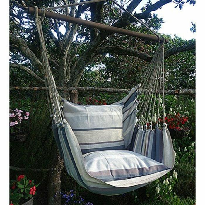 fauteuil suspendu avec repose pieds en tissu installé dans un jardin