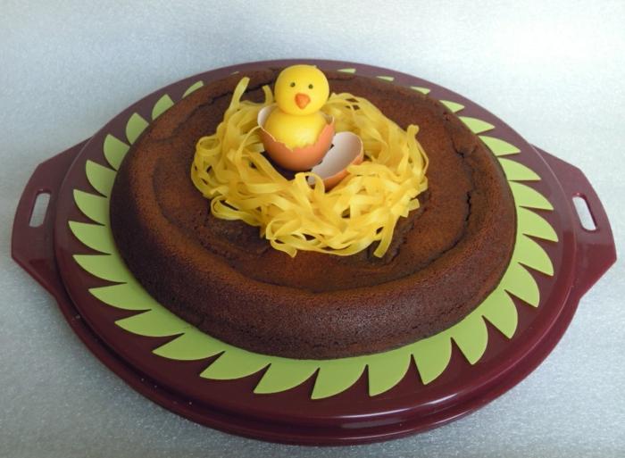 gâteau de chocolat décoré d'un nid avec une poule dedans