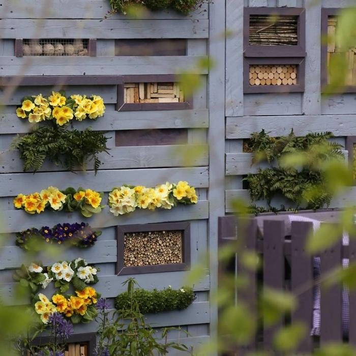 mur en palettes avec des fleurs et des abris à insectes