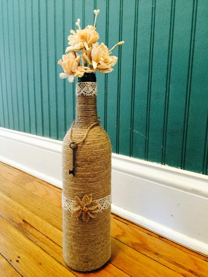Bouteilles recouvertes de corde vase et fleurs