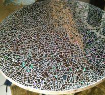 Table de jardin ronde avec une déco en mosaïque d\'anciens DVD