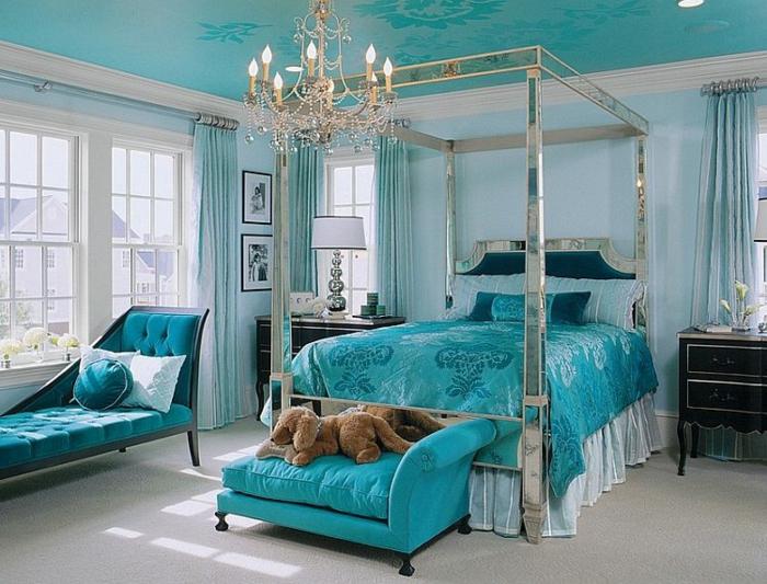 chambre bleu canard avec un lit argenté et lustre