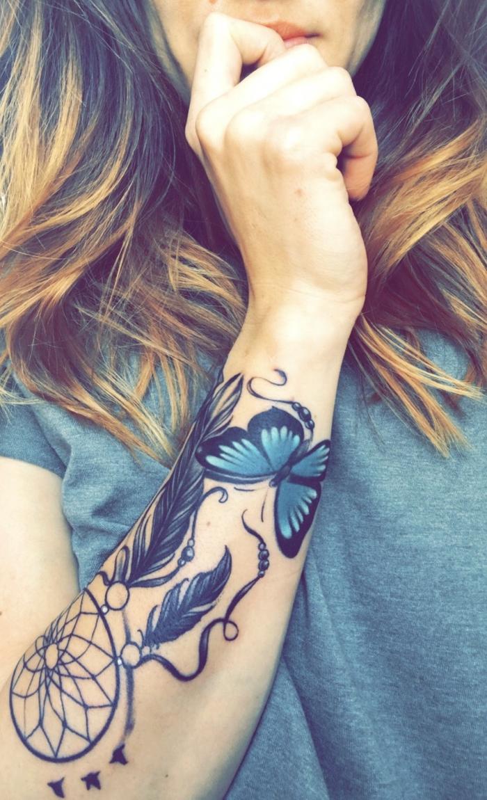 tatouage attrape-rêve bras cerceau et plumes papillon