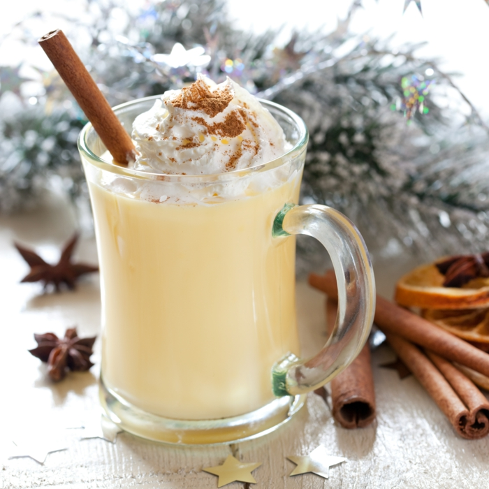 Fresh eggnog in a glass mug with wintry branches and spices