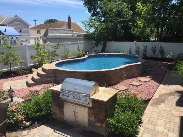 piscine semi-enterrée pierre jardin barbecue