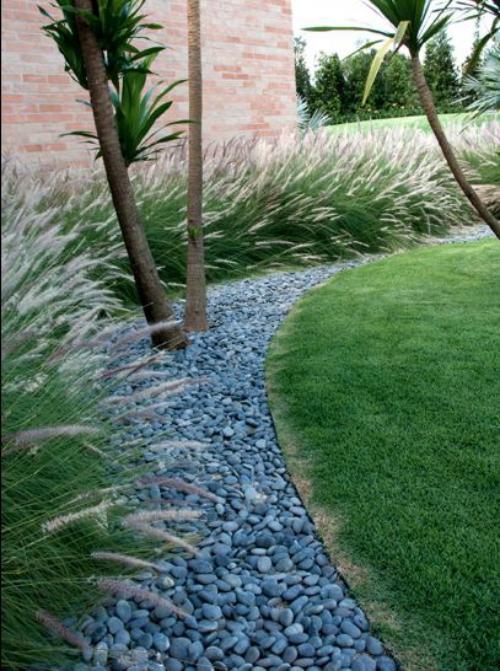 Décoration jardin avec galets gazon entouré d' un sentier