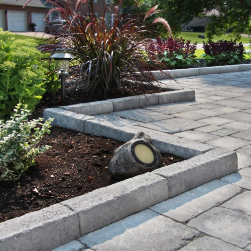 bordures de jardin sol dallé et maison au fond
