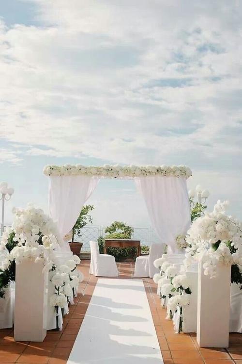 décoration mariage un porche de fleurs blanches et des rideaux blancs