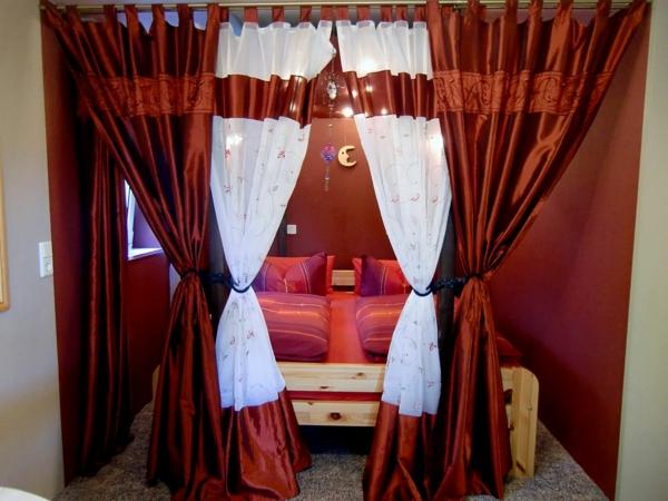 idée déco chambre adulte romantique lit en bois brut rideaux rouges