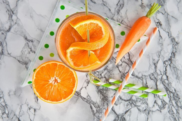 Fresh orange and carrot smoothie on marbled background