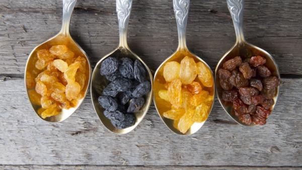 Raisins in metal spoons on wooden table
