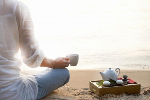 verre d' eau chaude le matin à la plage au lever du soleil