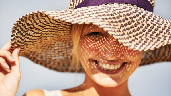 A gorgeous young woman wearing a straw hat in the summer sun
