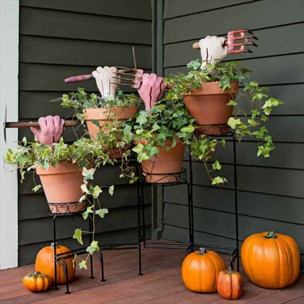 idée de décoration halloween extérieur fait maison mains de zombies dans les pots de fleurs