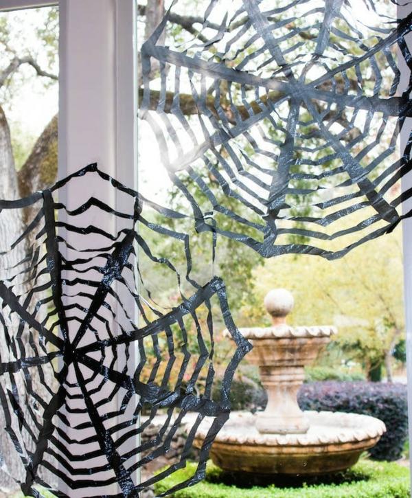 idée de déco extérieure pour halloween toile d'araignée faite en sac poubelle coupé en lanières