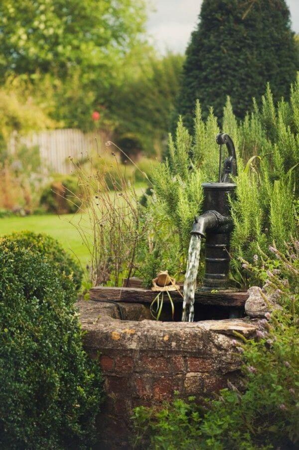 fontaine extérieure de jardin parmi les plantes