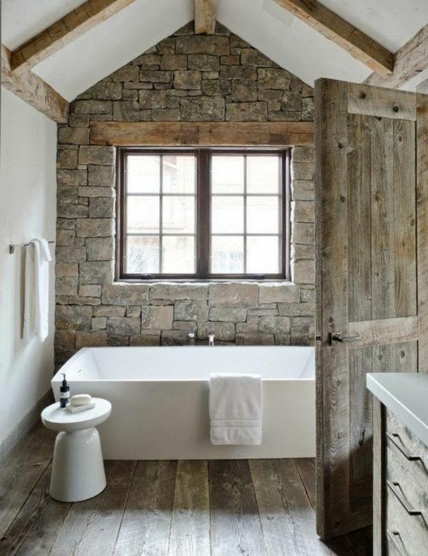 salle de bain sous comble sol en bois mur en pierre naturelle poutres apparentes