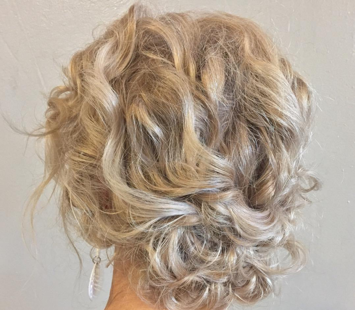 coupe cheveux bouclés élégant low updo