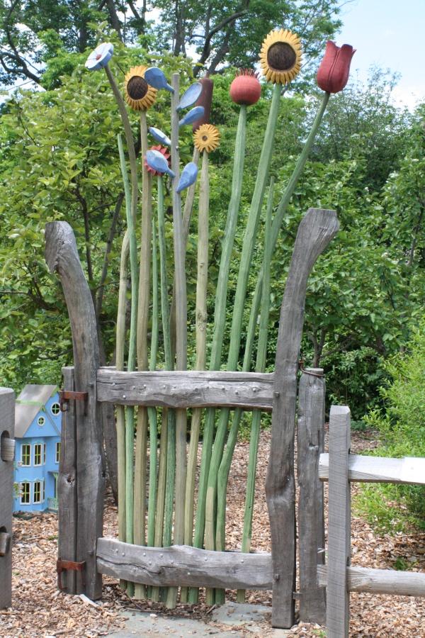 portillon de jardin en piquets de bois avec des éléments décoratifs en plastique