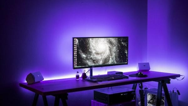 lumières néon de couleur bleue dans une chambre à coucher design avec grand bureau et grand écran pc
