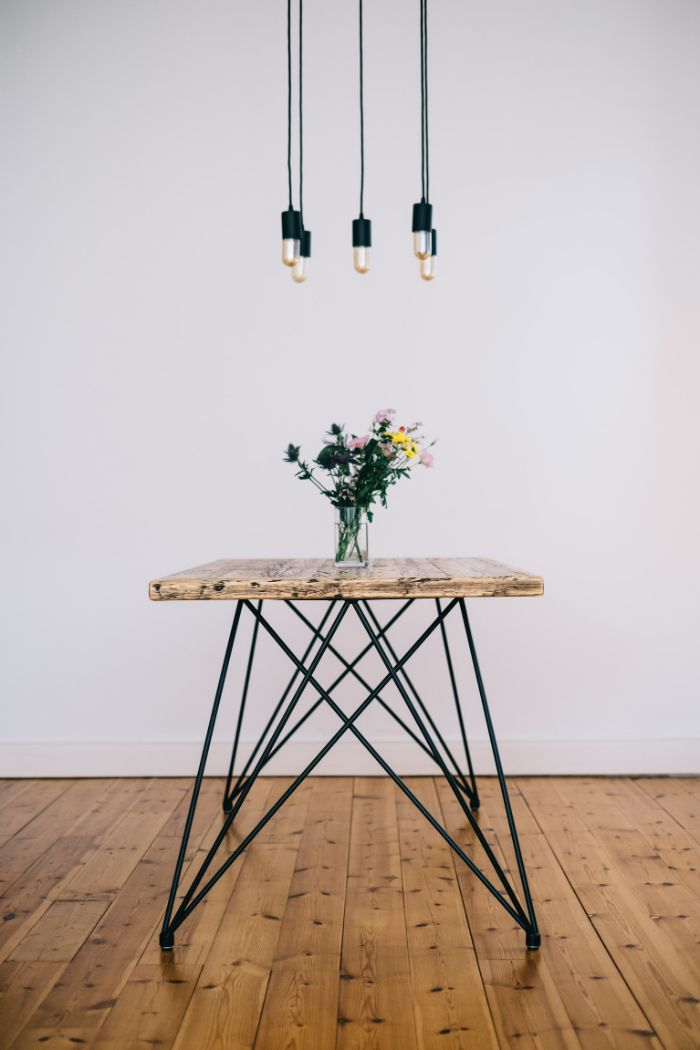 exemple de mobilier durable, table en plateau de bois brut et des pieds e épingle à cheveux sur sol parquet