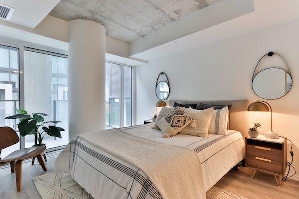 modèle de lampe élégante en laiton sur meuble de nuit bois dans une chambre blanche et bois