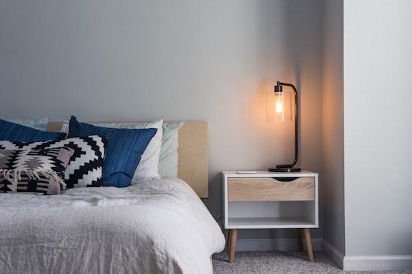 chambre industrielle avec lit surchargé de coussins, lampe de nuit industrielle sur table de nuit