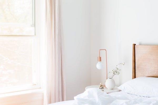 rideau rose clair, lampe ampoule laiton dans chambre blanche ambiance romantique chic