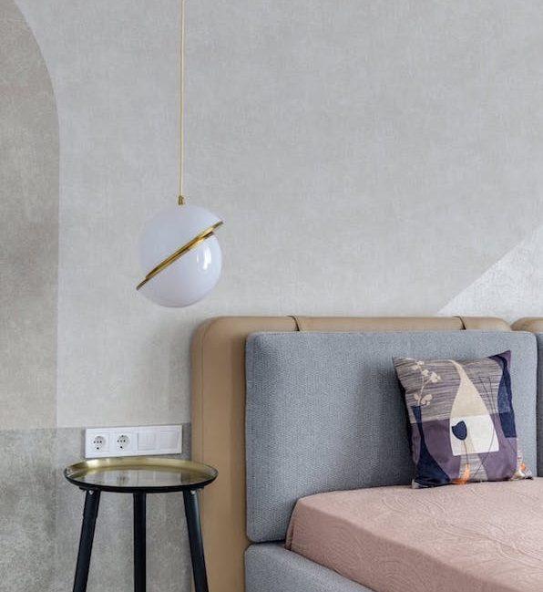 lampe blanc et laiton dans une chambre gris et marron, idée de suspension design originale côté lit