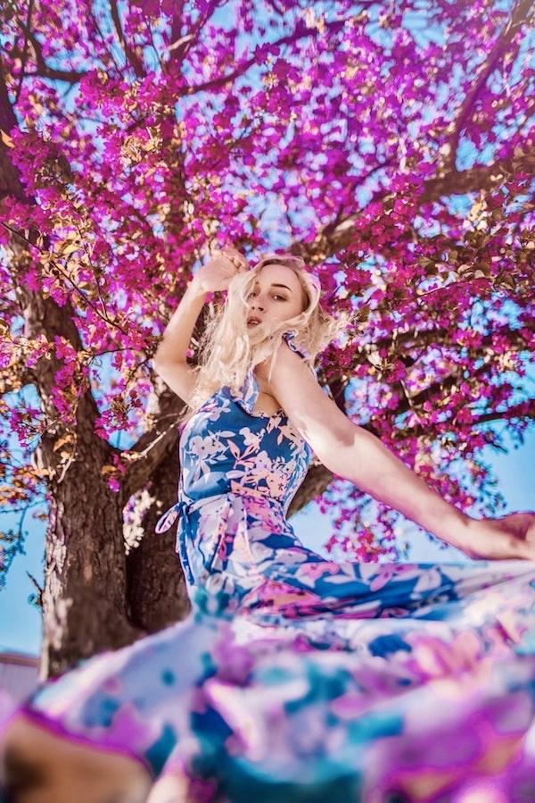 robe fleurie longue de couleur bleue avec des fleurs rose éparpillées, femme dessous un arbre aux fleurs fuchsia