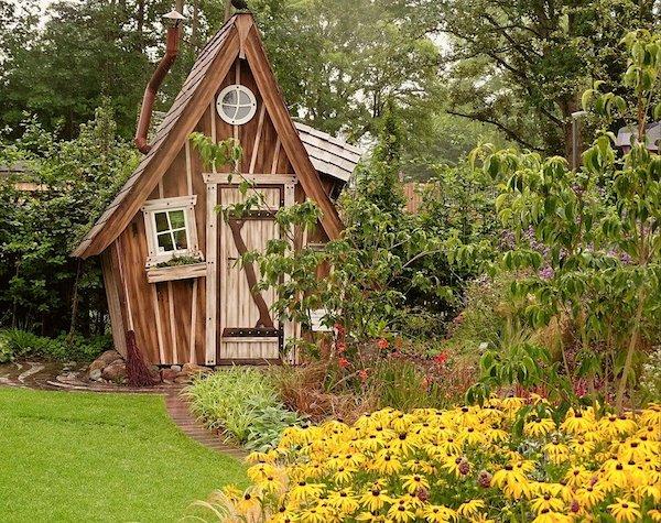 petites dalles posées en bordure de jardin avec haie fleurie avec arbustes et fleurs, maisonnette bois