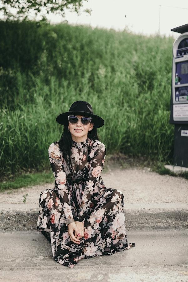 robe noire manche longue transparente avec des fleurs pivoines, accessoirisée de chapeau et lunettes de soleil