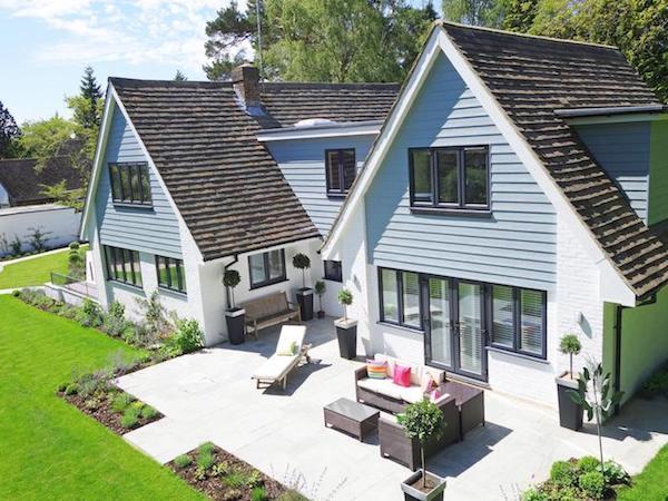 bordure de jardin aux arbustes et herbes fraiches, maison double et gazon adjacent