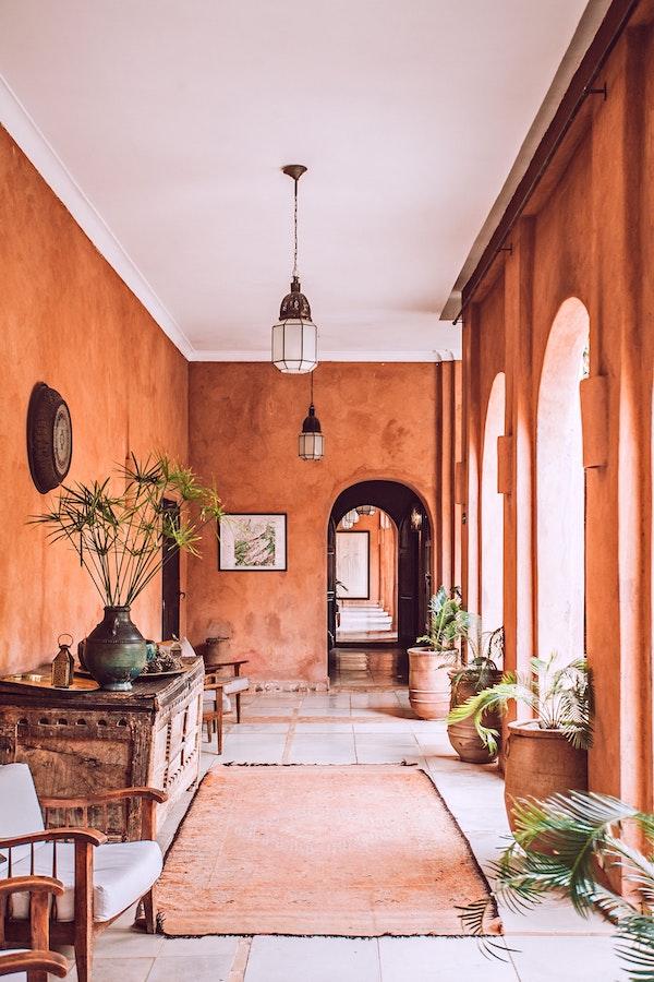 hall d entrée aux murs de couleur terracotta et mobilier vintage marocain