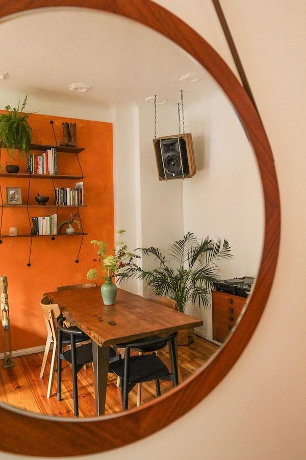 salle à manger rustique avec mur terracotta orangé et mobilier de bois brut